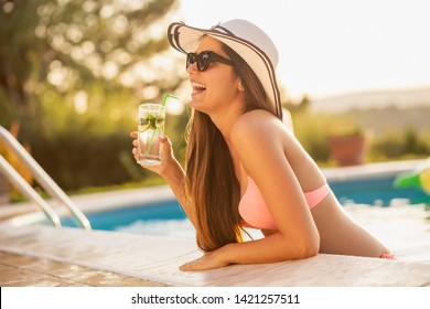 Attractive young woman wearing bikini, sunglasses and a hat, drinking cocktails by the swimming pool edge and having fun