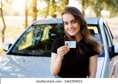 Attractive young woman wearing black T-shirt standing in front of modern car bragging about receiving driving license showing licence to the camera and feeling happy