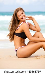 An attractive young woman wearing a black bikini sits on a beach with her elbow on her knee and her hand to her head.  Surf can be seen in the background. Vertical shot.