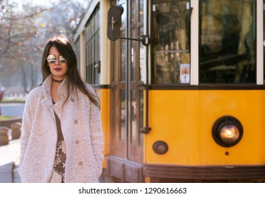 Attractive young woman wearing gray coat with long dark hair and sun glasses posing outdoor in Milan streets, Italy. Beautiful caucasian model portrait. Strit fashion