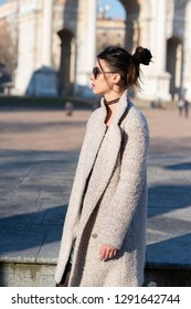 Attractive young woman wearing gray coat with long dark hair and sun glasses posing outdoor in Milan streets, Italy. Beautiful caucasian model portrait. Steet fashion