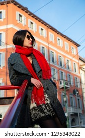 Attractive young woman wearing gray coat with long dark hair red scarf and with sun glasses posing outdoor in Milan streets near metro station. Beautiful caucasian model portrait, street fashion
