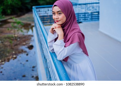 Attractive young woman wearing hijab walking on street.Beautiful Muslim girl wearing hijab.Muslim Hijab Fashion Portraiture.