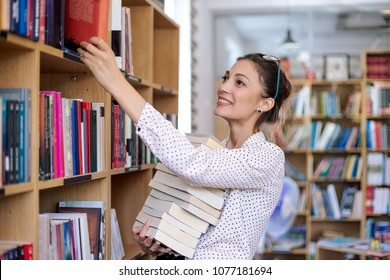 Attractive young woman wearing pink pale shirt with dots and fashionable glasses holding a stack of books in the library surrounded by bookshelves with colorful books.