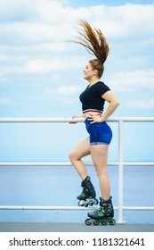 Attractive young woman wearing roller skates relaxing after ride. Fit female having fun during summer time on sea coast.
