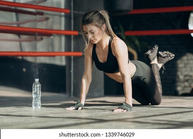 Attractive young woman wearing a sports bra and shorts doing pushups in a gym