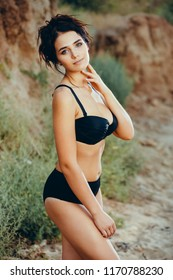 2369e83d294 Attractive young woman wearing stylish black high-rise bikini standing near  the hills