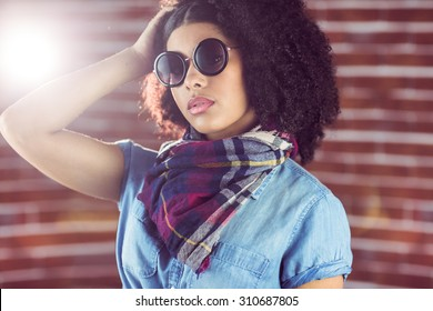 Attractive young woman wearing sunglasses against red brick background