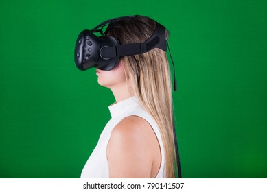 attractive young woman wearing virtual reality headset in green screen studio
