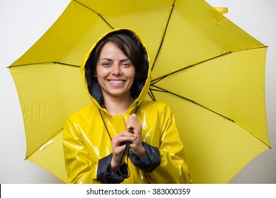 Attractive young woman wearing a yellow raincoat and holding an umbrella
