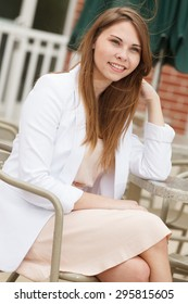 An attractive young woman with a white blazer
