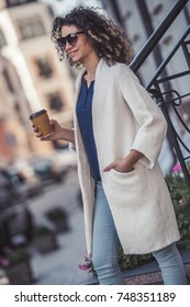 Attractive young woman in white coat and sun glasses is drinking coffee and smiling while walking in the city