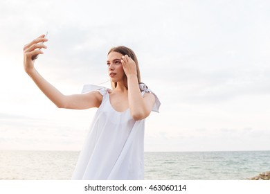 Attractive young woman in white dress making selfie with cell phone on the beach