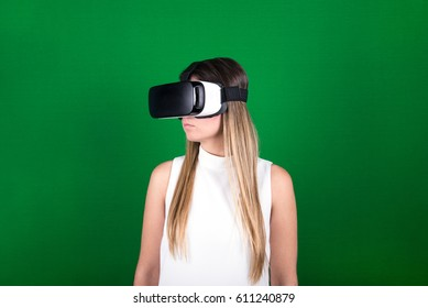 attractive young woman in white dress looking through virtual reality headset, green screen background, futuristic concept