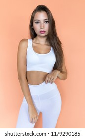 Attractive young woman in white sports top and leggings on a beige background.