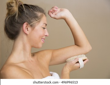 Attractive young woman in white towel holding dry brush to under side of upper arm