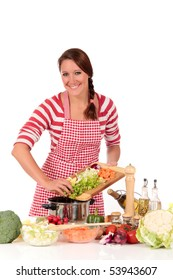 Attractive Young woman working in kitchen, preparing soup.  Bowls with vegetables in foreground.  Studio, white background.