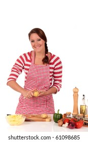Attractive Young woman working in kitchen, cutting, cleaning vegetables potatoes. Studio, white background.