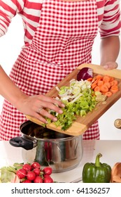Attractive Young woman working in kitchen, preparing soup.    Studio, white background.