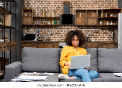 attractive young woman working working with laptop on couch