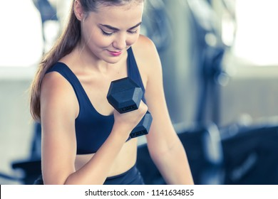 Attractive young woman working out with dumbbells at a fitness gym.