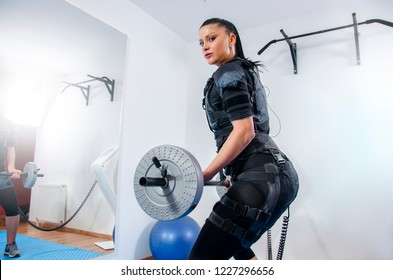 Attractive young woman working out in EMS suit