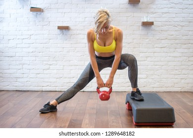 Attractive young woman working out with kettle bell and doing squats on stepper. Squat side lifts – Woman standing on the side of the bench and leaving one foot on the floor and holding weight.