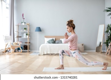 Attractive young woman working out on white mat at home. Yoga exercises in bedroom.