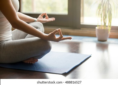 Attractive young woman working out at home, doing yoga exercise on blue mat, sitting in Easy (Decent, Pleasant Posture), meditating, breathing, relaxing. Body close-up, focus on hand