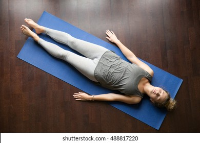 Attractive young woman working out at home, doing yoga exercise on blue mat, lying in Shavasana (Corpse or Dead Body Pose), resting after practice, meditating, breathing. Full length, view from above