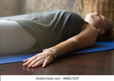 Attractive young woman working out at home, doing yoga exercise on blue mat, lying in Shavasana (Corpse or Dead Body Posture), resting after practice, meditating, breathing. Close-up, focus on hand