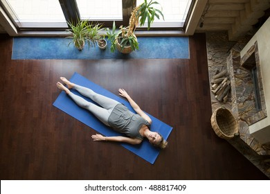 Attractive young woman working out in living room, doing yoga exercise on blue mat, lying in Shavasana (Corpse, Dead Body Posture), resting after practice, meditating, breathing. Full length, top view