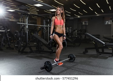 Attractive young woman working out with bar. Fitness girl sexy in red sport wear posing and smiling in gym.