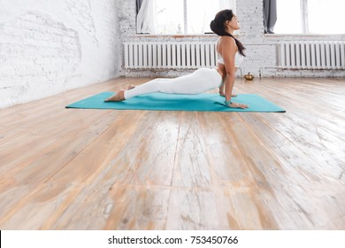 Attractive young woman working out indoors. Attractive model doing exercises yoga on wooden floor. Standing in upward-facing dog pose against a white brick wall and big window. urdhva mukha svanasana