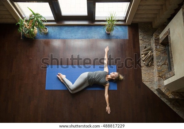 Attractive young woman working out in living room, doing yoga exercise on wooden floor, lying in Belly Twist Pose, Jathara Parivartanasana, resting after practice, full length, top view
