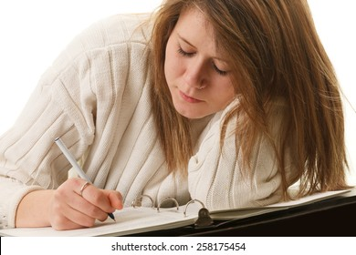 An attractive young woman writing on a notebook.