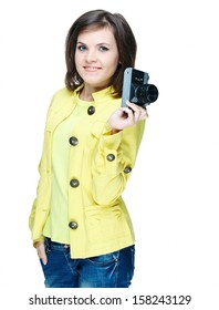 Attractive young woman in a yellow jacket. Holds the camera. Isolated on white background