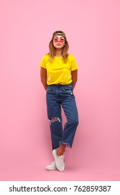 Attractive young woman in yellow T-shirt, jeans and glasses standing on pink background and looking at camera.