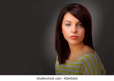 An attractive young woman in a yellow and white striped top.