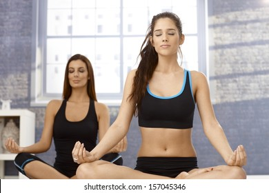 Attractive young women sitting in tailor seat eyes closed, practicing yoga, meditating.