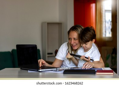 Attractive young women working on laptop while her son sitting on her lap and watching cartoons on tablet.Single mom and her son looking at digital computer at home.Copy space.Technology concept.