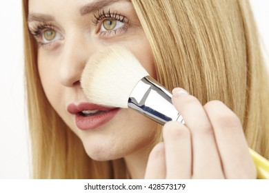 An attractvie young blond woman uses a big brush for powder on her face.