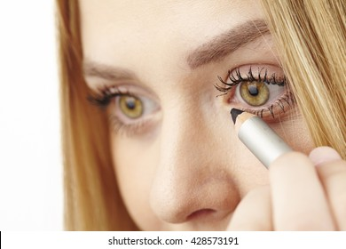 An attractvie young blond woman uses kohl under her eye.
