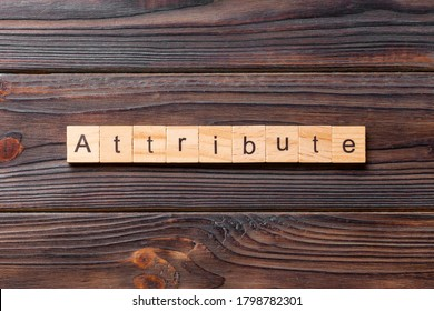 ATTRIBUTE word written on wood block. ATTRIBUTE text on cement table for your desing, concept.