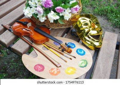 Attributes of the arts. Art palette, brushes, violin, bow, theater mask, a bouquet of roses and jasmine on a garden bench.
