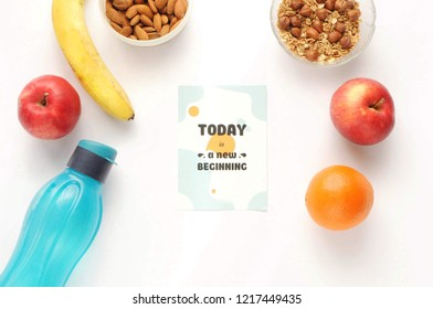 Attributes of a healthy lifestyle: food, sports and athlete's equipment on white background with motivated phrase. Flat view with copy space. Eco bottle, nuts, oatmeal and fruits.