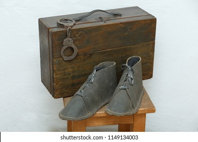 Attributes of the prisoner: boots, suitcase and handcuffs on the nightstand.