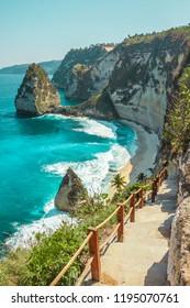The Atuh beach, Nusa Penida island near Bali, Indonesia. Ocean waves, cliffs and a desert beach with tropical plants