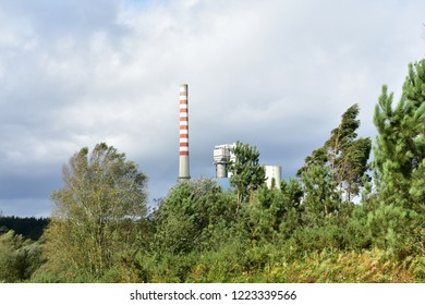 Atumn landscape with power station. Red and white long smoking chimney. Trees, bushes and grass. Cloudy, grey sky.