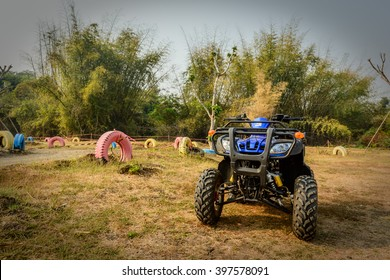 ATV, an all-terrain vehicle, also known as a quad, quad bike, three-wheeler, four-wheeler, or quadricycle, parking beside the race track